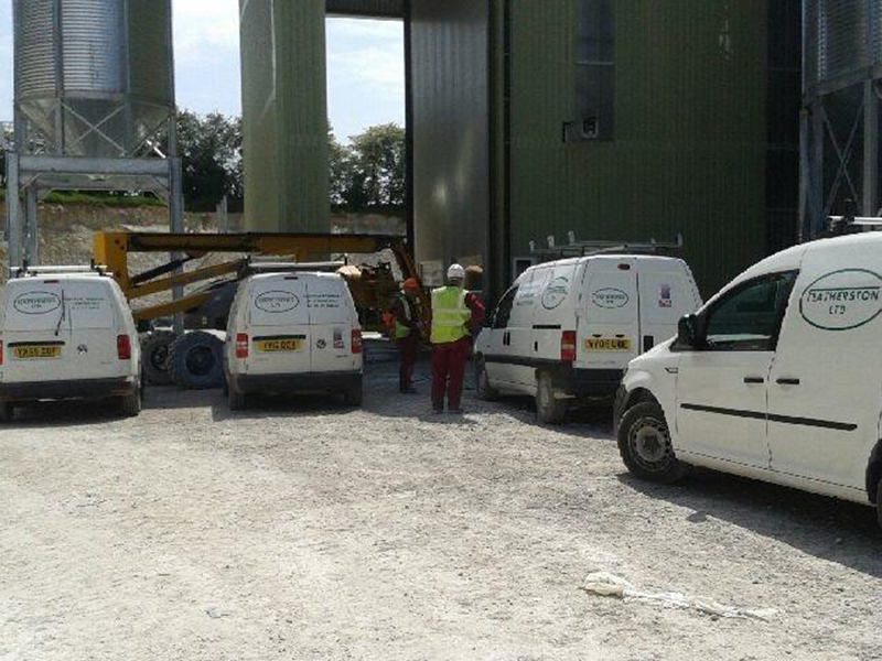 Vans and men on site
